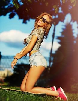 Portret van schattige grappige sexy jonge stijlvolle lachende vrouw meisje model in heldere moderne doek met perfecte zonovergoten lichaam buiten in het park in jeans broek met skateboard in glazen