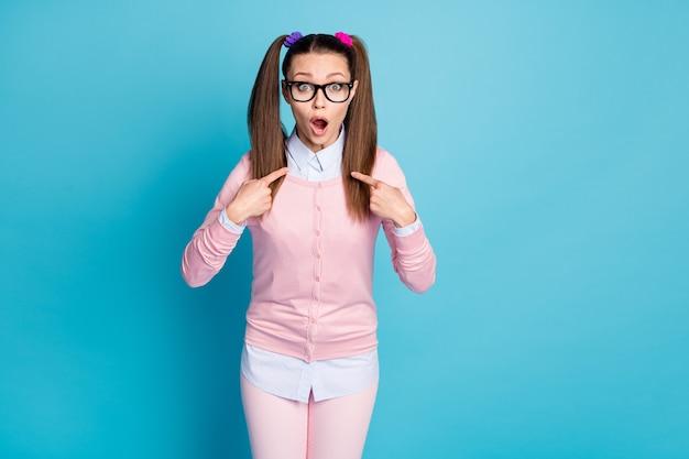 Portret van schattige grappige verlegen meisjesachtige verbaasde studente die naar zichzelf wijst