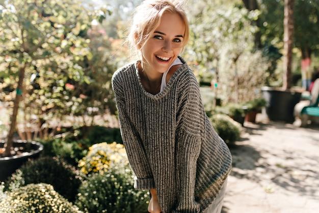 Portret van schattige groenogige vrouw in wit t-shirt en gebreide trui glimlachend in botanische tuin.