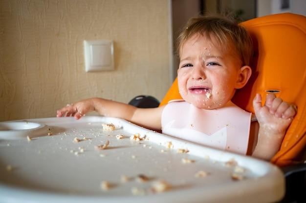 Portret van schattige huilende baby peuter zittend met eettafel