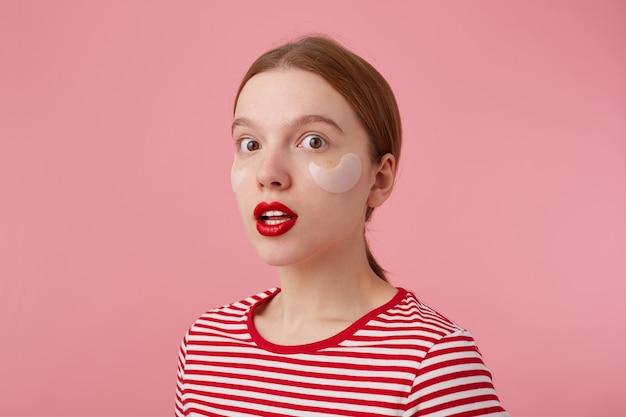 Portret van schattige jonge amazwd roodharige dame in een rood gestreept t-shirt, met rode lippen en met vlekken onder de ogen, angstige blikken, stands.