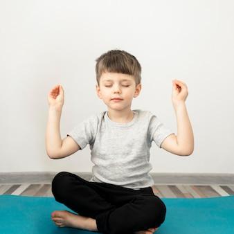 Portret van schattige jonge jongen het beoefenen van yoga