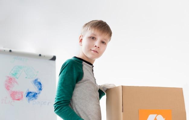 Portret van schattige jonge jongen leren hoe te recyclen