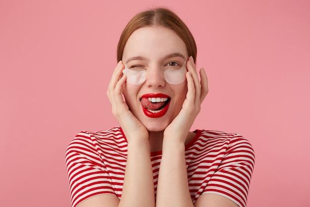 Portret van schattige jonge knipogende roodharige dame met vlekken onder de ogen, met rode lippen en, draagt in een rood gestreept t-shirt, kijkt en toont tong, staat.
