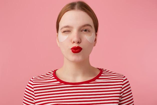 Portret van schattige jonge lachende roodharige vrouw met rode lippen en met vlekken onder de ogen, draagt in een rood gestreept t-shirt, kijkt en knipoogt, stuurt kus, staat.
