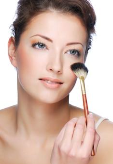Portret van schattige jonge volwassen vrouw schoonmakende gezicht na het aanbrengen van make-up