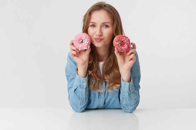 Portret van schattige jonge vrouw met lang blond golvend haar, houdt donuts bij het gezicht, geïsoleerd op witte achtergrond.