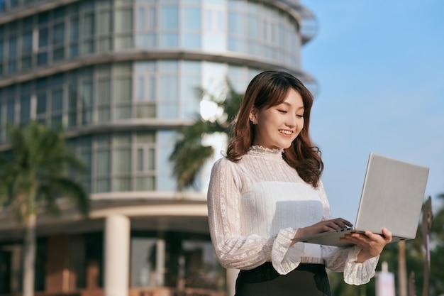 Portret van schattige jonge zakenvrouw buiten met koffie en laptop