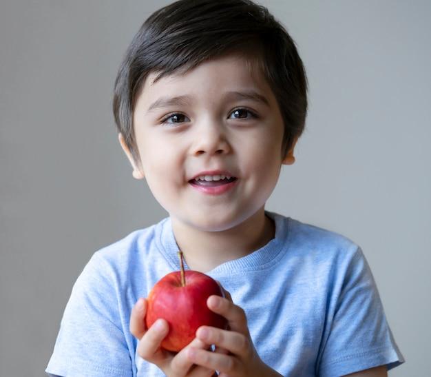 Portret van schattige jongen jongen organische rode appel te houden op zijn hand en camera te kijken