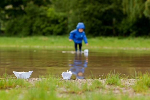 Portret van schattige jongen jongen spelen met handgemaakte schip. kleuterjongen die een speelgoedboot vaart langs de waterkant in het park