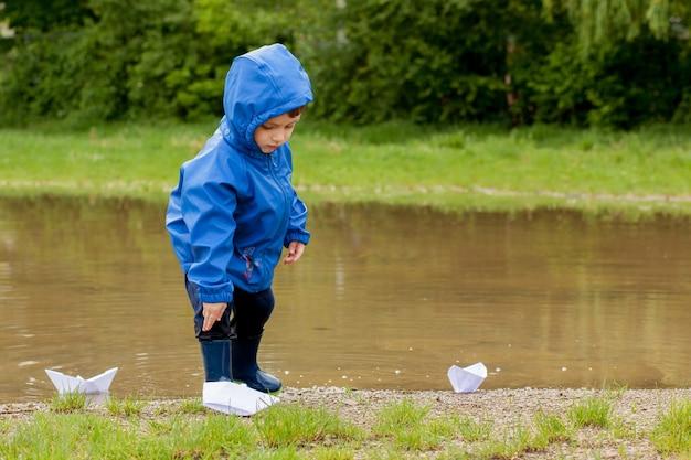 Portret van schattige jongen jongen spelen met handgemaakte schip. kleuterschooljongen die een speelgoedboot vaart door de waterkant in het park.