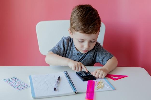 Portret van schattige jongen jongen thuis huiswerk maken. weinig geconcentreerd kind dat binnen met kleurrijk potlood schrijft.
