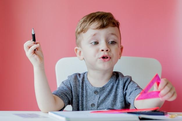 Portret van schattige jongen jongen thuis huiswerk maken. weinig geconcentreerd kind schrijven