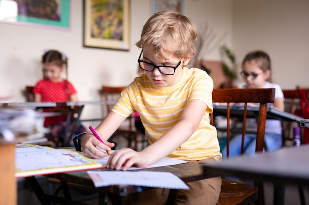 Portret van schattige jongen met schets pen en papier aan balie in klas.