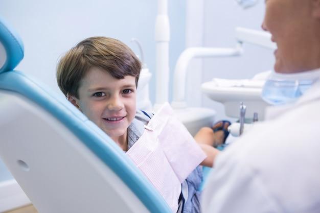 Portret van schattige jongen zittend op tandarts stoel door tandarts