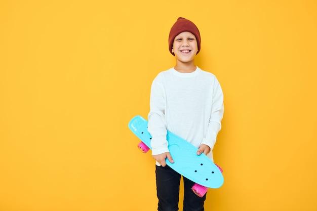 Portret van schattige jongens casual blauwe skateboard gele kleur achtergrond