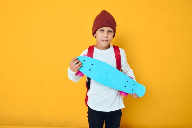 Portret van schattige jongens met rode rugzak blauwe skateboard studio levensstijl