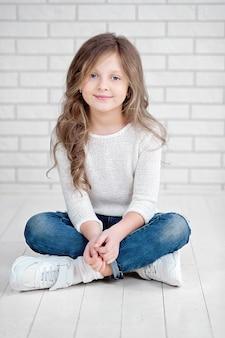 Portret van schattige kleine 7 jaar oud meisje glimlachend en zittend op witte houten vloer