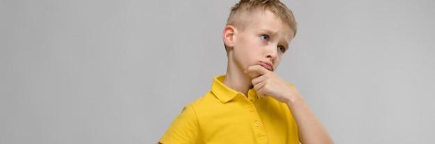Portret van schattige kleine blonde blanke jongen in geel t-shirt onzeker verbaasd op grijze achtergrond