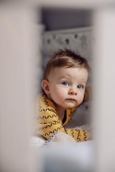 Portret van schattige kleine blonde peuter liggend op buik, met droevig gezicht