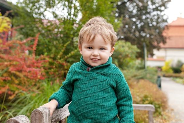 Portret van schattige kleine jongen gelukkig lief lachend kind in het park kijk naar de camera