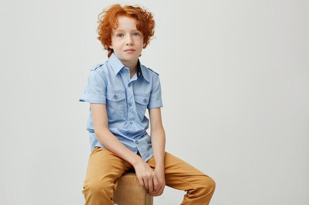 Portret van schattige kleine jongen met krullend gember haar op zoek met ernstige expressie, zittend op een doos