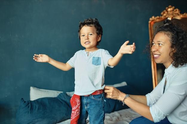 Portret van schattige kleine jongen met krullend haar staande op bed, positieve emoties uitdrukken, jonge moeder zoon kijken met trots en genegenheid.