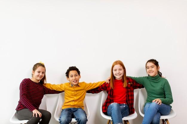 Portret van schattige kleine kinderen in spijkerbroek zittend in stoelen tegen de witte muur