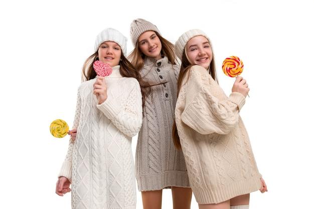 Portret van schattige kleine kinderen meisjes in stijlvolle gebreide trui met snoep camera kijken en lachend tegen witte studio muur. kindermode concept