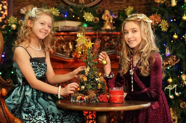 Portret van schattige kleine meisjes in de buurt van versierde kerstboom
