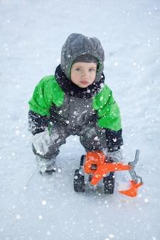 Portret van schattige kleine peuter zittend op sneeuw en spelen met zijn gele tractor speelgoed in het park