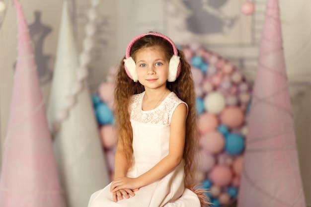 Portret van schattige kleine prinses in koptelefoon. studio achtergrond met ballen en kegels