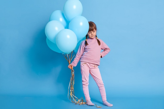 Portret van schattige kleuter poseren tegen blauwe muur met ballonnen