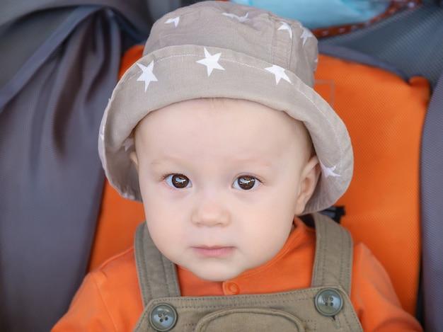 Portret van schattige lachende baby in panamahoed zittend in kinderwagen