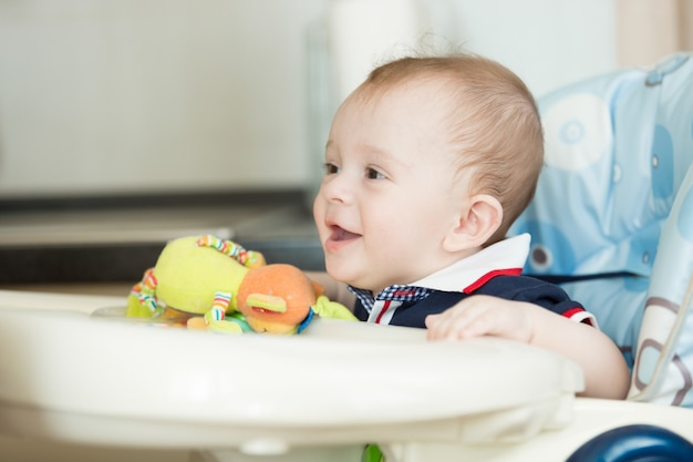 Portret van schattige lachende babyjongen zittend in de kinderstoel in de keuken