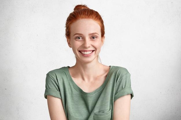 Portret van schattige lachende gember vrouw heeft blije uitdrukking als geslaagd voor examens of zomersessie, poseert tegen witte betonnen muur
