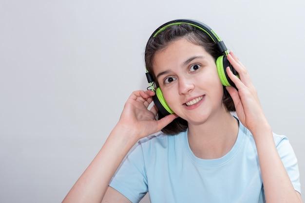 Portret van schattige lachende positieve meisje tiener luisteren naar muziek in groene koptelefoon op wit