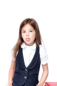 Portret van schattige lachende schoolmeisje toont tong, geïsoleerd op een witte achtergrond.
