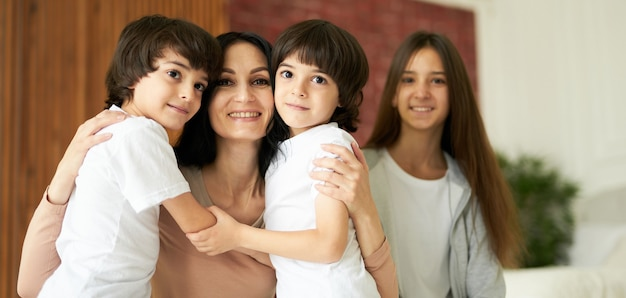 Portret van schattige latijnse kinderen, kleine tweelingjongens die naar de camera kijken en hun moeder knuffelen