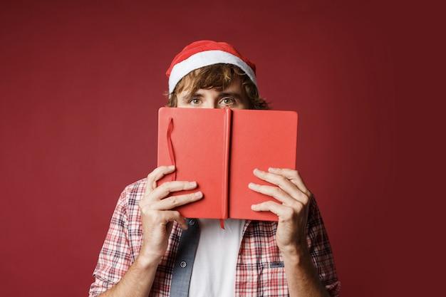 Portret van schattige man verstopt achter het boek