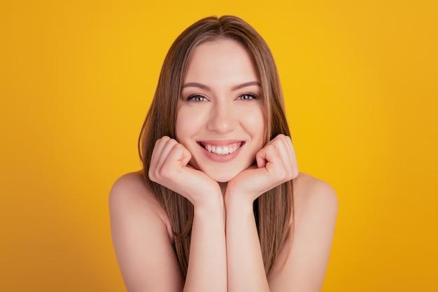 Portret van schattige mooie prachtige droom dame vuisten kin stralende witte glimlach op gele achtergrond