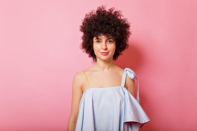 Portret van schattige mooie vrouw met kort krullend haar draagt blauw shirt glimlacht op roze