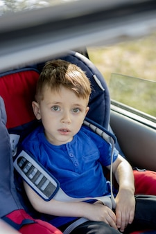 Portret van schattige peuter jongen zitten in autostoel. veiligheid bij het vervoer van kinderen