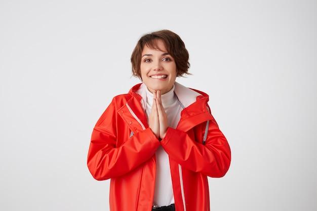 Portret van schattige positieve jonge kortharige dame in witte golf en rode regenjas, bijt op de lippen, kijkt omhoog, glimlachen, maakt gebedgebaar. staand.