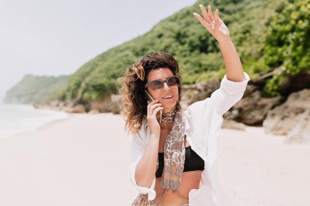 Portret van schattige romantische vrouw gekleed zwarte top, wit overhemd gesprekken op smartphone