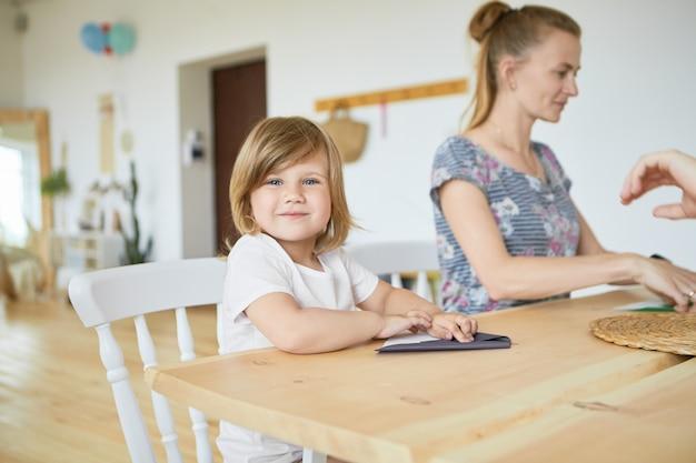 Portret van schattige schattige babymeisje in wit t-shirt zittend aan houten eettafel met haar moeder, leren hoe ze origami papier vliegtuig maken, met een gelukkige glimlach. selectieve aandacht