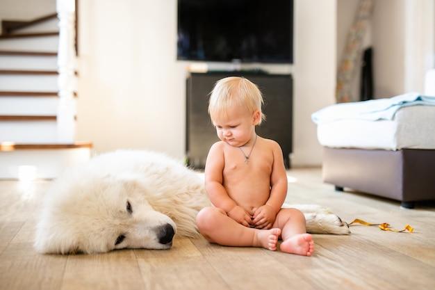 Portret van schattige schattige kleine blonde babyjongen zittend met hond thuis. glimlachend kind met dierlijk huisdier. gelukkig jeugdconcept
