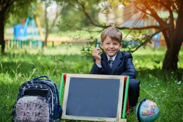 Portret van schattige school jongen in het park, zonnige dag