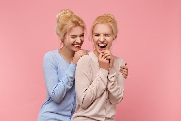 Portret van schattige tweelingblonden die zich nooit samen vervelen, omdat ze altijd grappen maken en plezier hebben. stads over roze achtergrond.