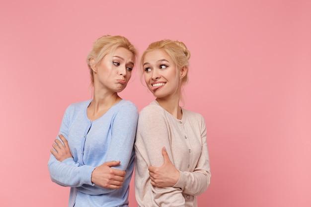 Portret van schattige tweelingblonden, gekke meisjes staan met hun rug naar elkaar toe, grimassen en kijken elkaar aan. staat op roze achtergrond.